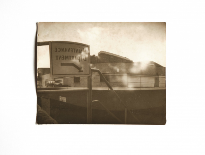 Pinhole image of a sign in front of a maintenance building